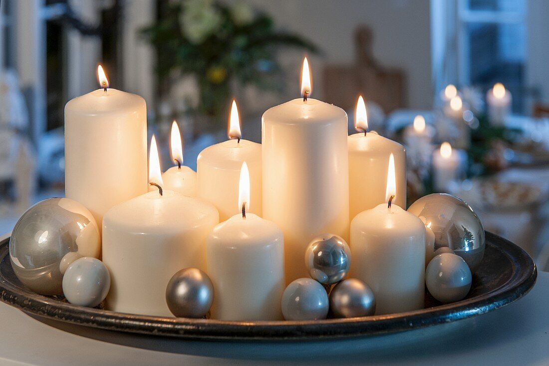 Lit white pillar candles of various sizes and silver baubles on tray