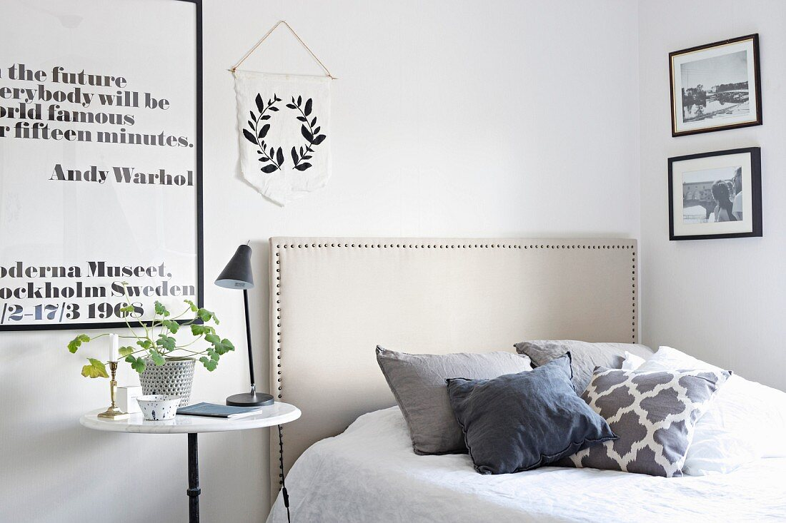 Scatter cushions on bed with fabric headboard, bedside lamp on bistro table and black and white framed motto on wall