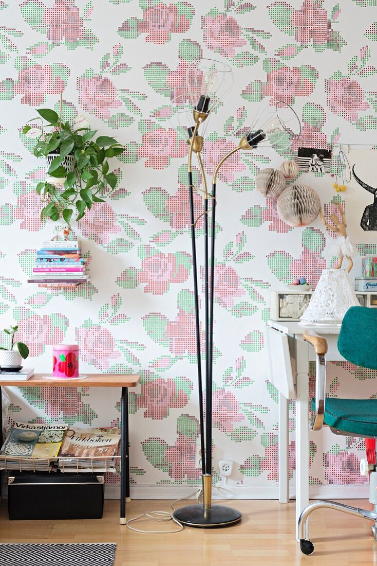 Retro standard lamp in front of wallpaper with floral cross-stitch pattern
