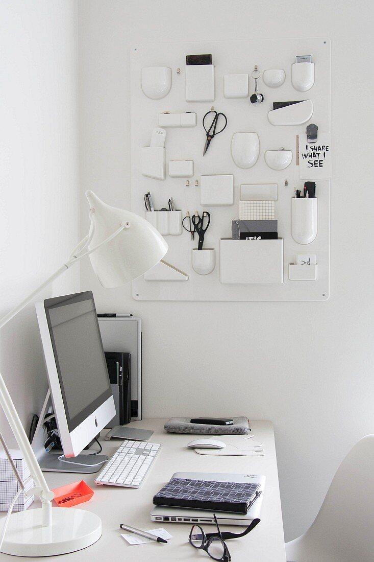 Monitor and white table lamp on white desk in corner below white, plastic retro organiser on wall