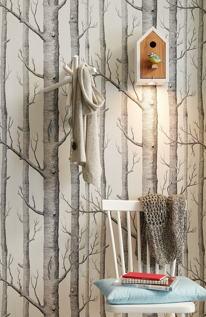A bird house with a built in spotlight hung on a wall with tree-patterned wallpaper