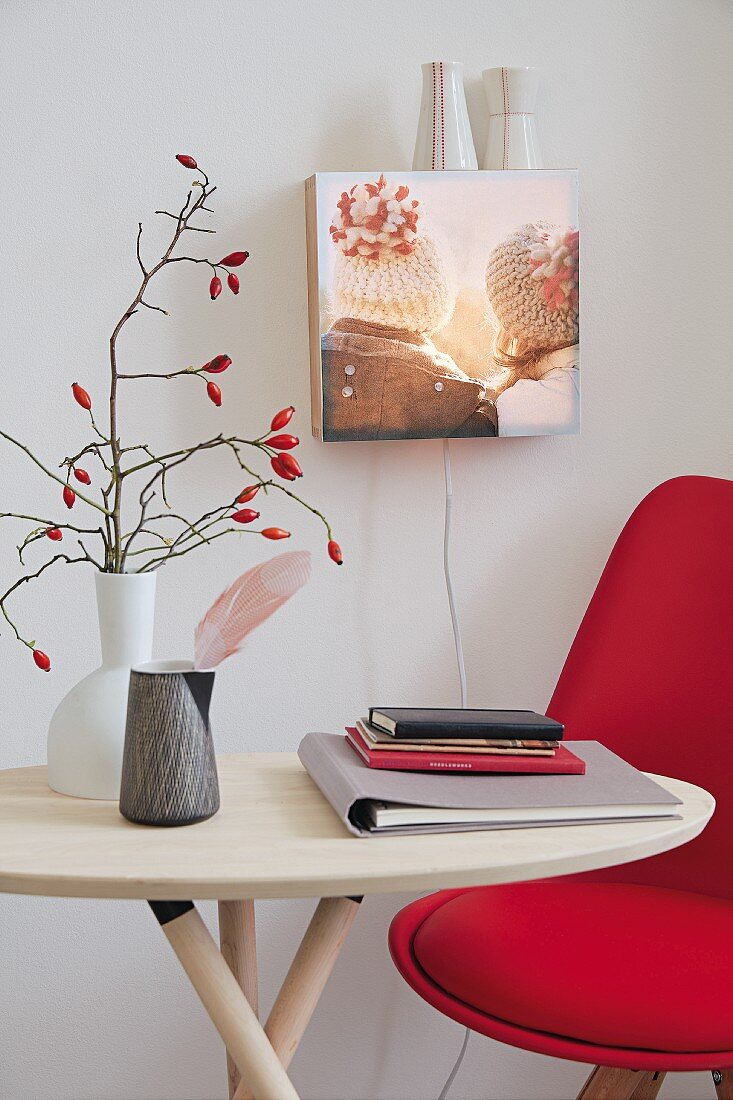 A DIY wall light made from a light box with a photo with a table and a red chair in front of it