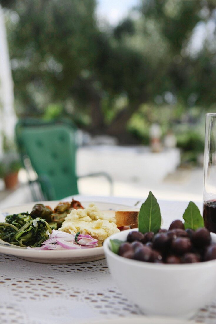 Dishes of antipasti and olives on table