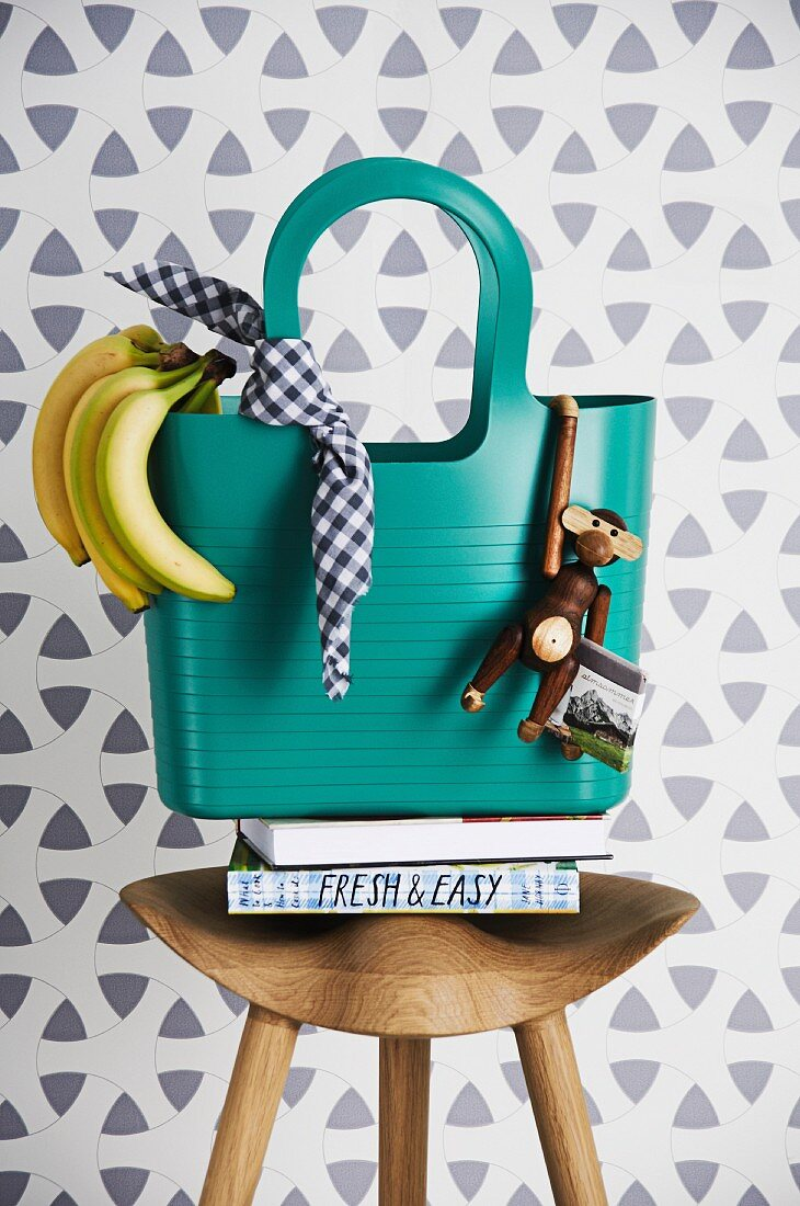 Türkise Einkaufstasche auf Hocker dekoriert im Dschungellook mit Bananen & Holzäffchen