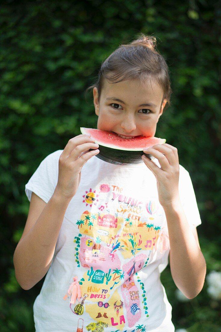 Girl eating watermelon in garden