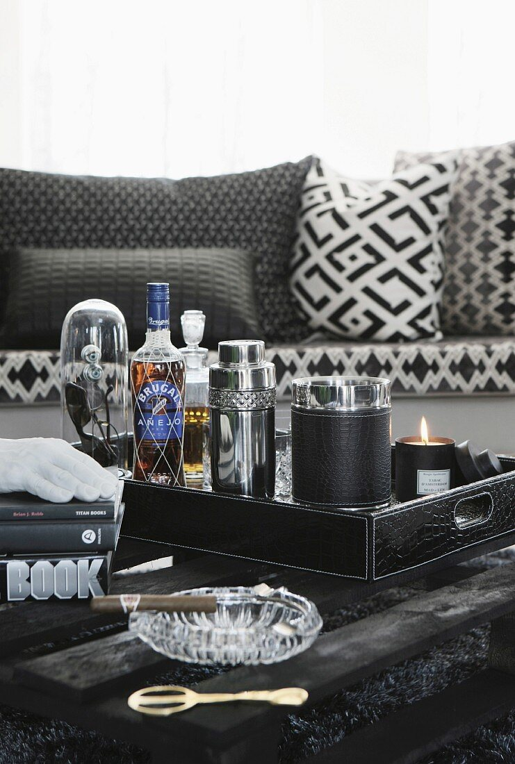 Minibar with cocktail shaker on tray and cigar in ashtray on black table made from pallet in front of sofa