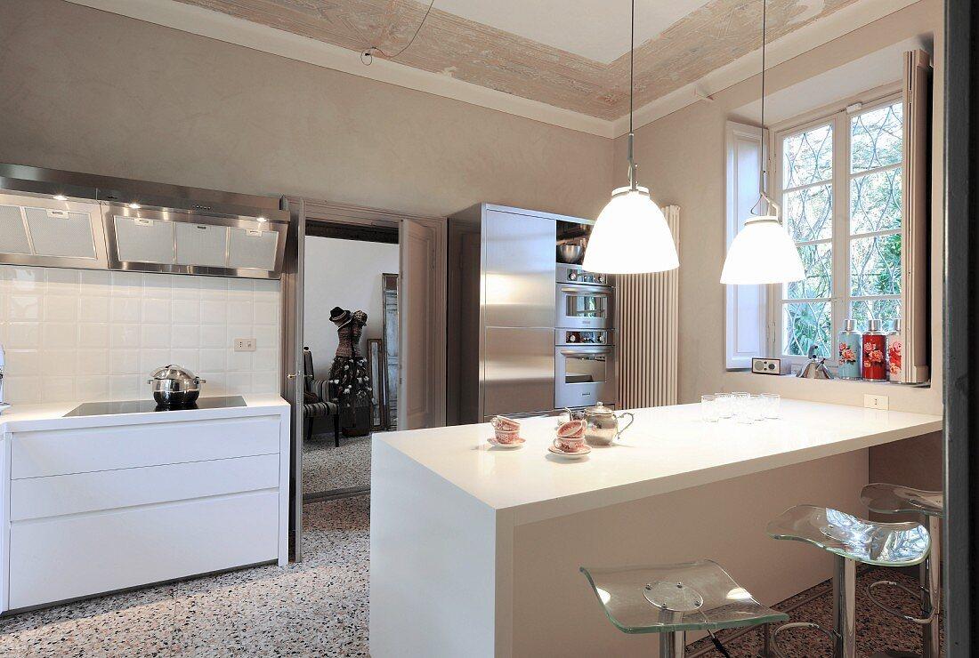 White kitchen counter below pendant lamps in open-plan kitchen