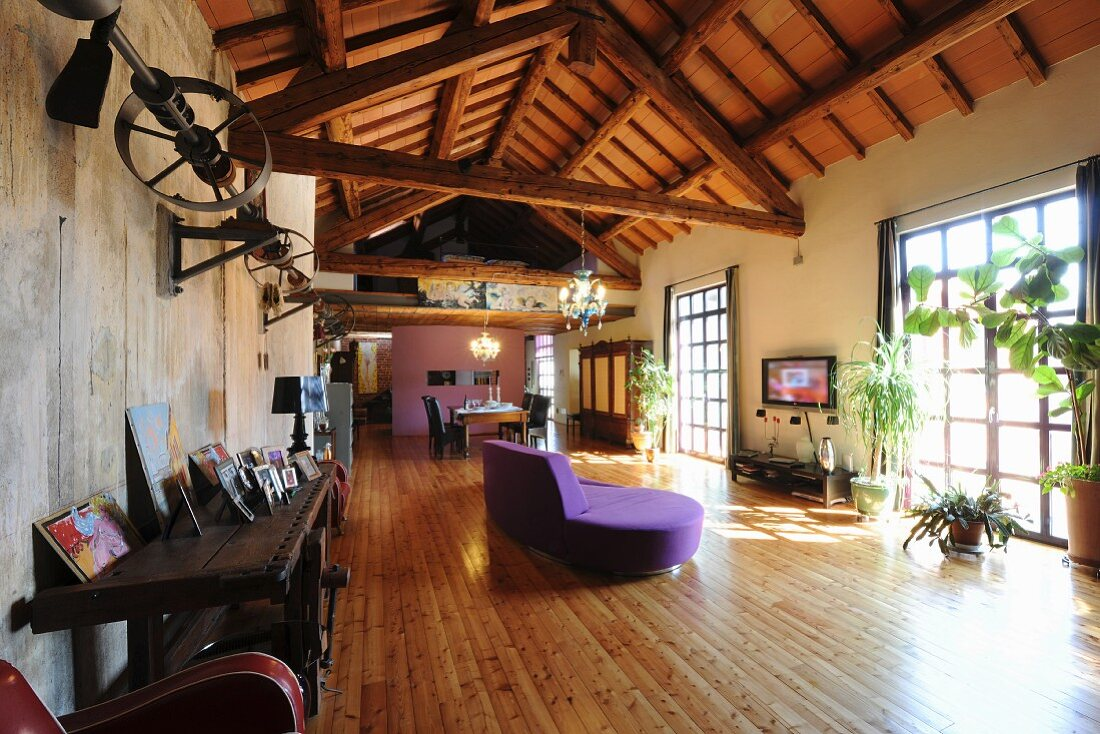 Wooden roof structure, purple sofa and larch flooring in loft apartment