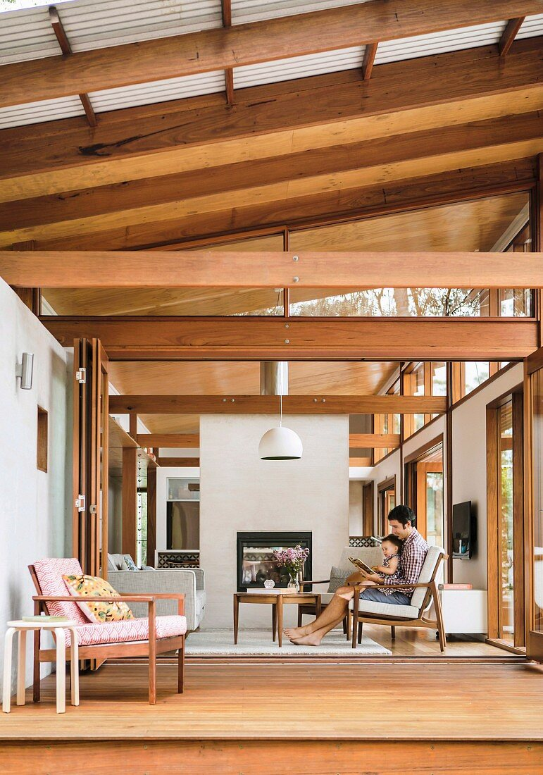 View of wooden terrace and living room with wooden construction and simple Asian flair, father and child on a comfortable armchair