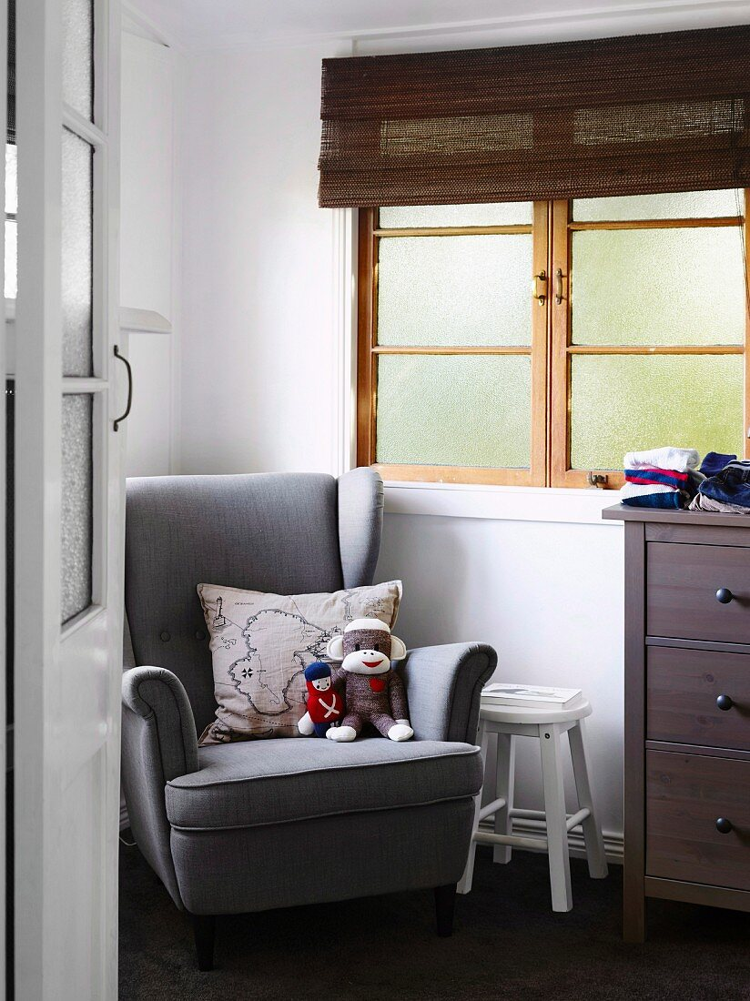 View through open room door to gray reading armchair with soft toys and pillows, next to lattice window with bamboo blind in the children's room