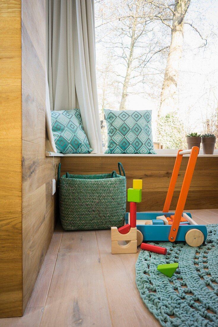 Modern wood-clad walls, window seat and wooden toys on oak floor in corner