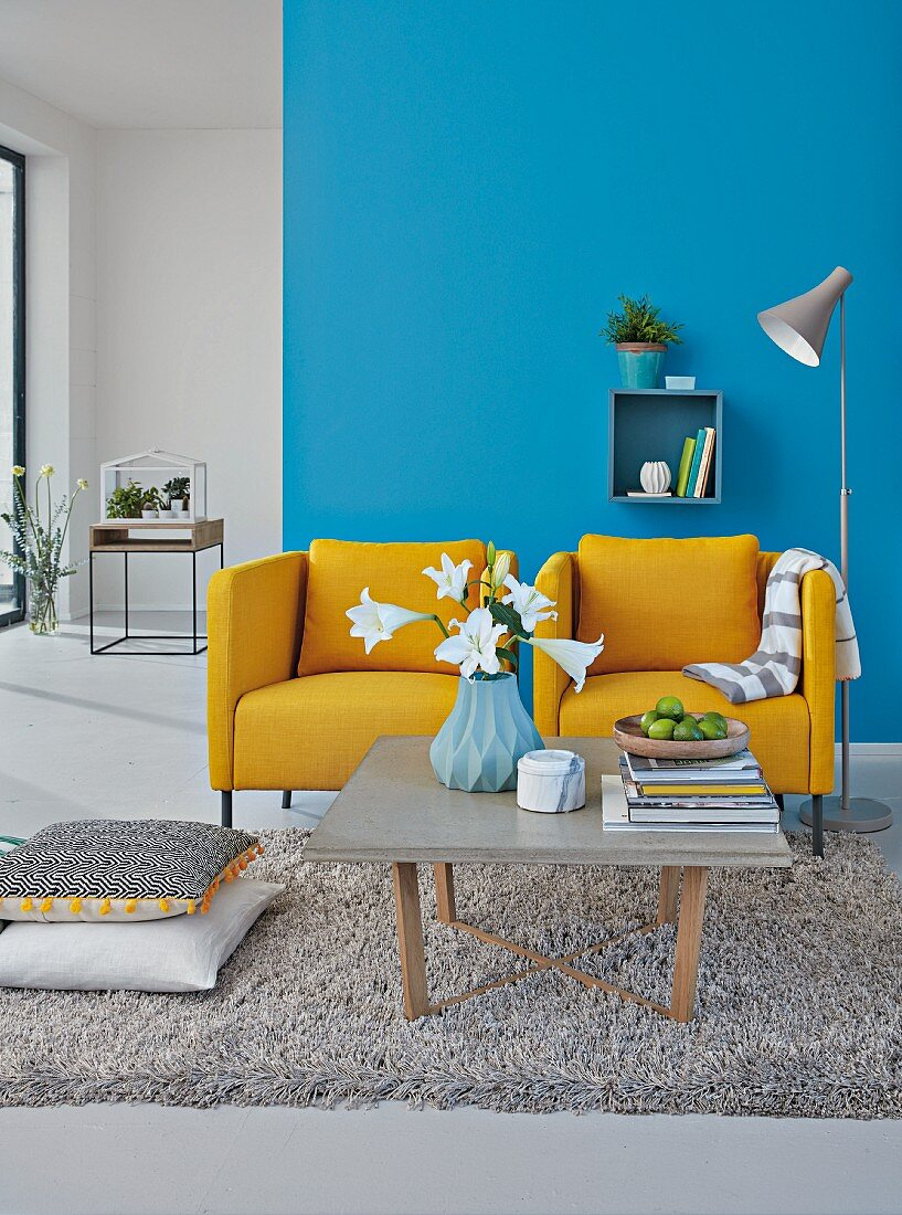 Two mustard-yellow upholstered armchairs against a blue wall with a coffee table with a concrete surface on a shag pile rug