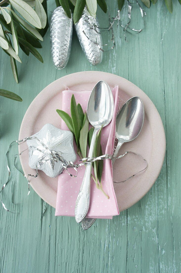 Kleine Löffel mit einem Olivenzweig und Schneeflocken-Schokolade in Stanniolpapier