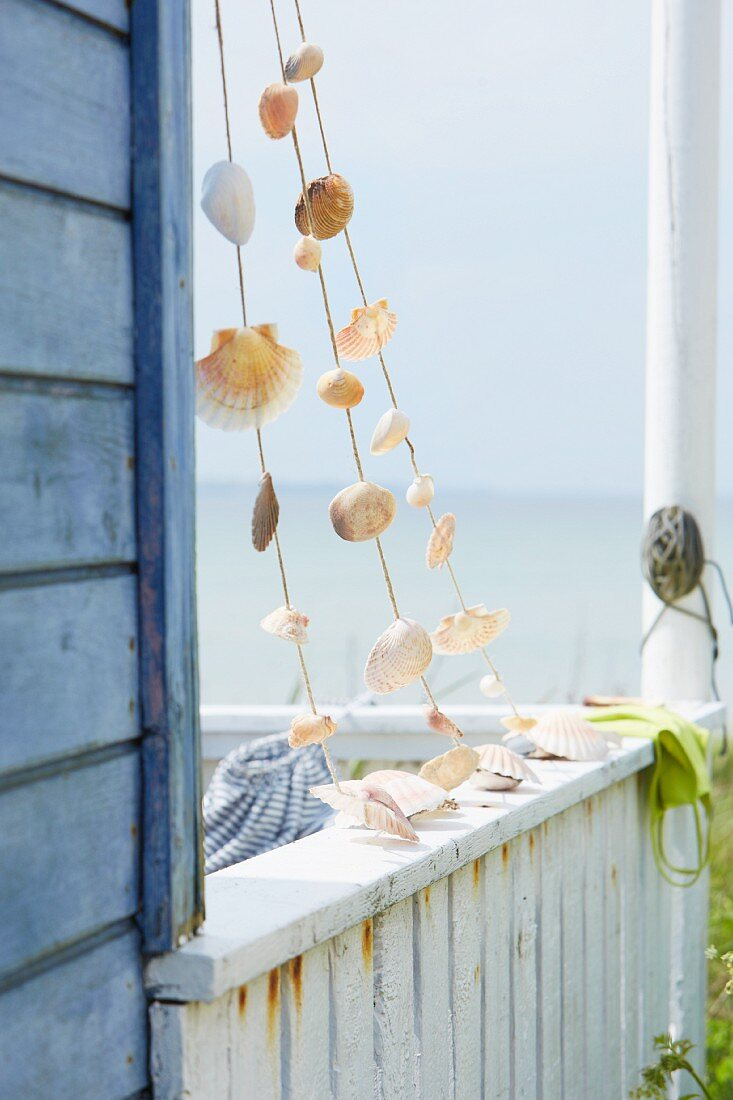 Garland of shells on balcony of wooden seaside cabin