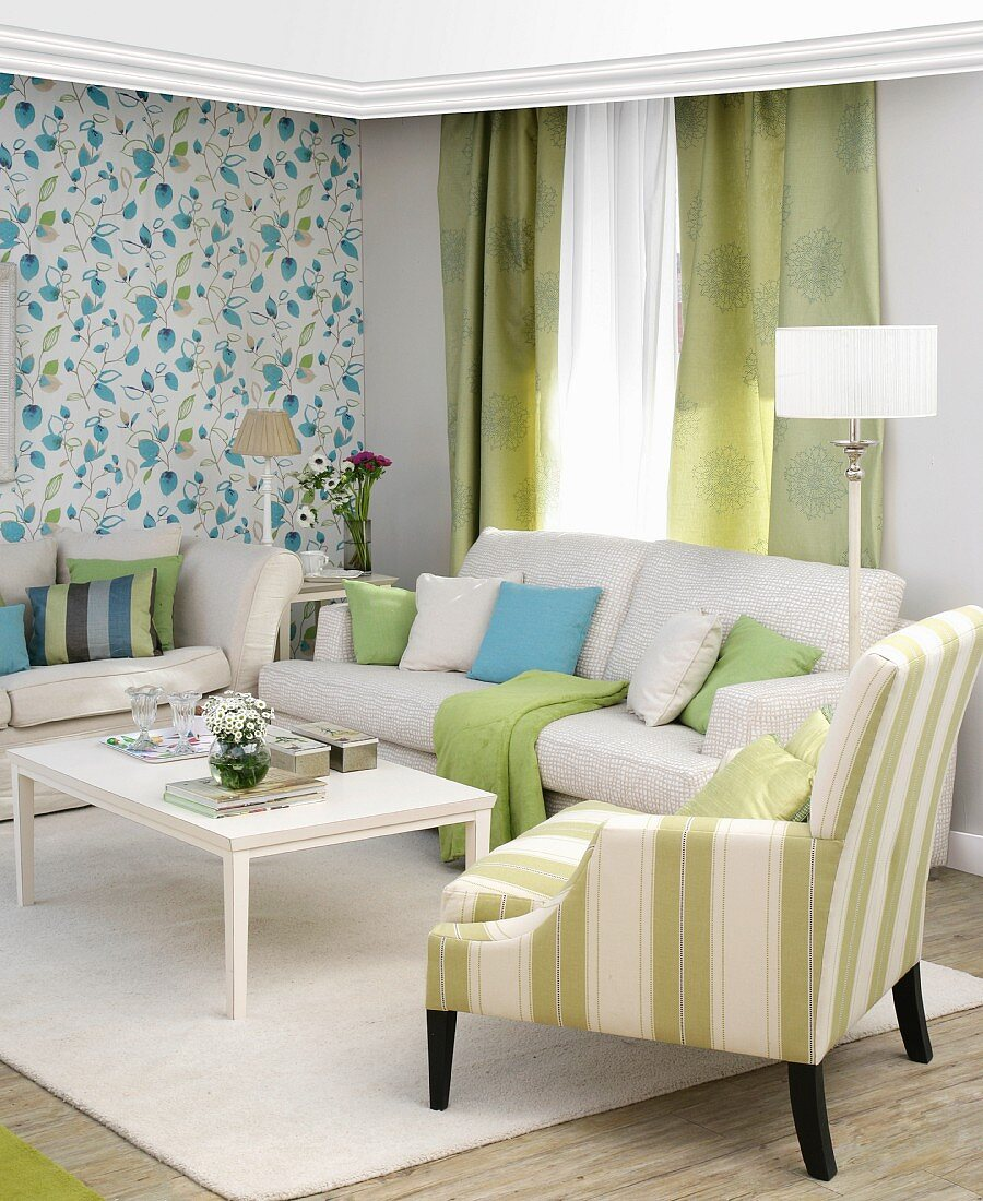 Upholstered furniture and patterned wallpaper in classic living room in white, blue and green