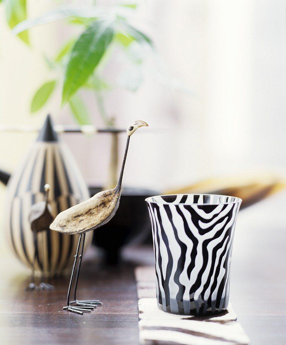 Vogelskulptur neben einem Windlicht mit Zebramuster