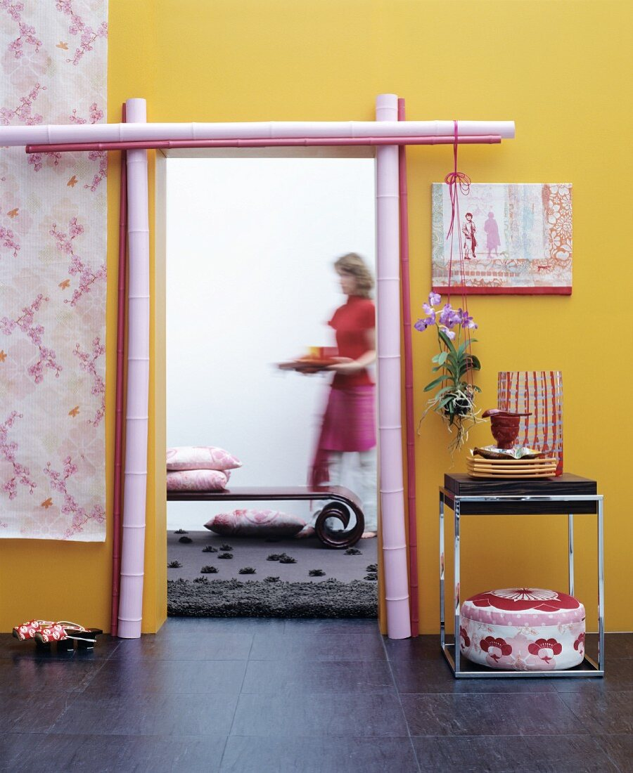 Open doorway frames with painted bamboo poles in yellow wall