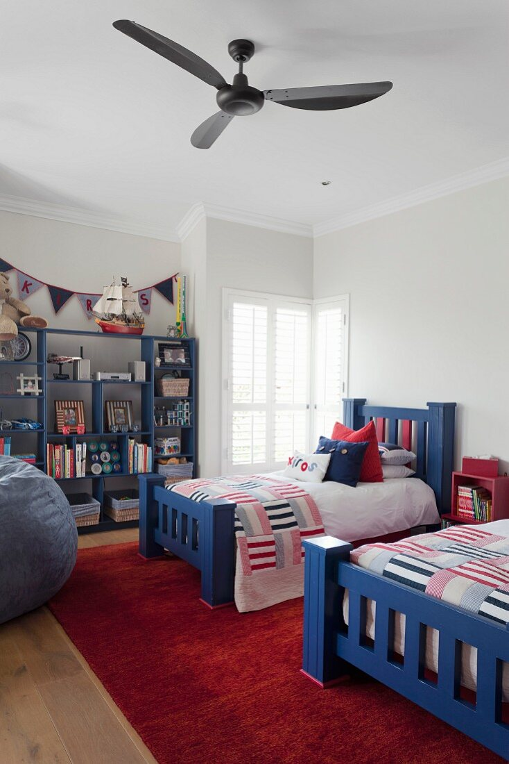 Twin beds with chunky, blue-painted wooden frames and patchwork bedspreads below ceiling fan