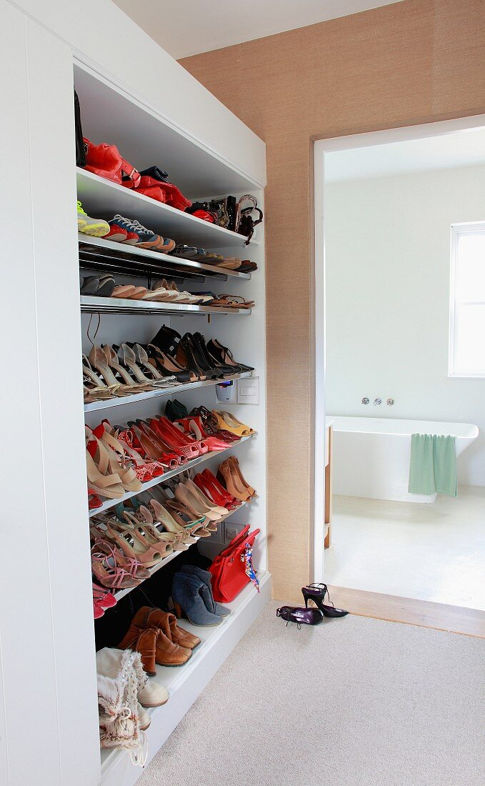 Open-plan, floor-to-ceiling shoe rack next to bathroom entrance with view of modern bathtub