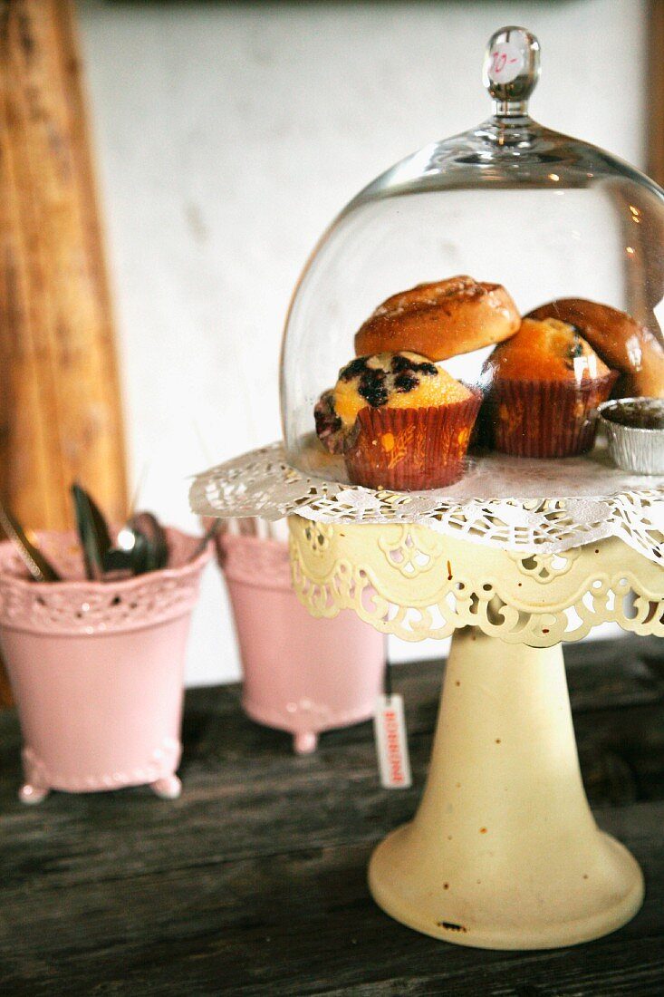 Muffins under glass cover on vintage, pastel yellow cake stand