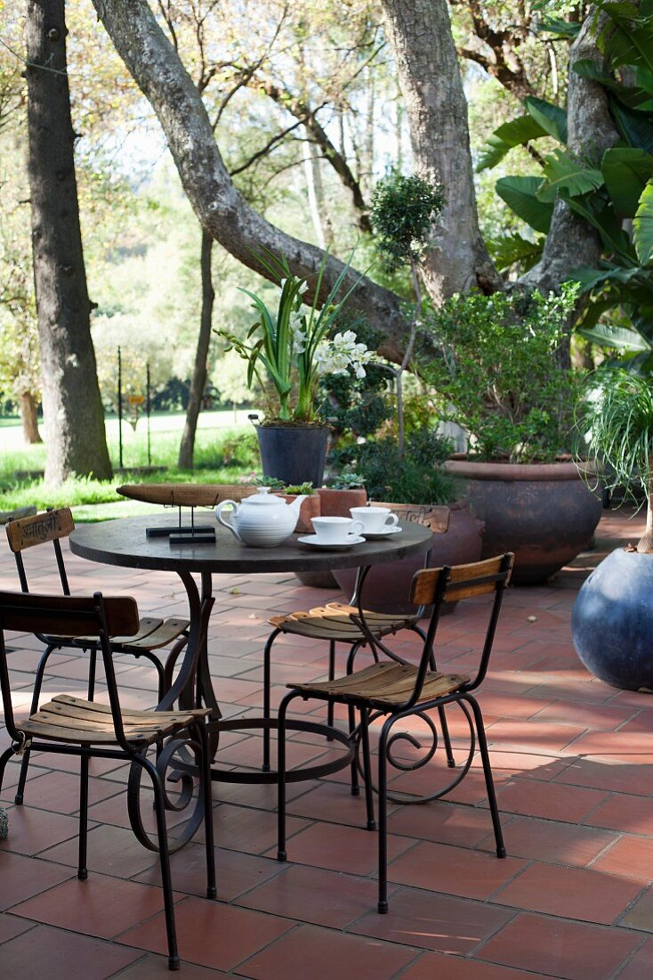 Garden chairs and table with ornate frame on terrace below trees