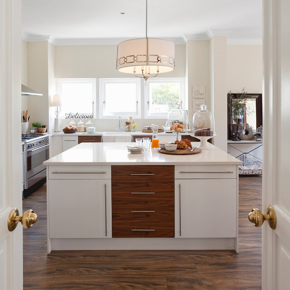 View through open double doors into open-plan kitchen with white and wooden island counter