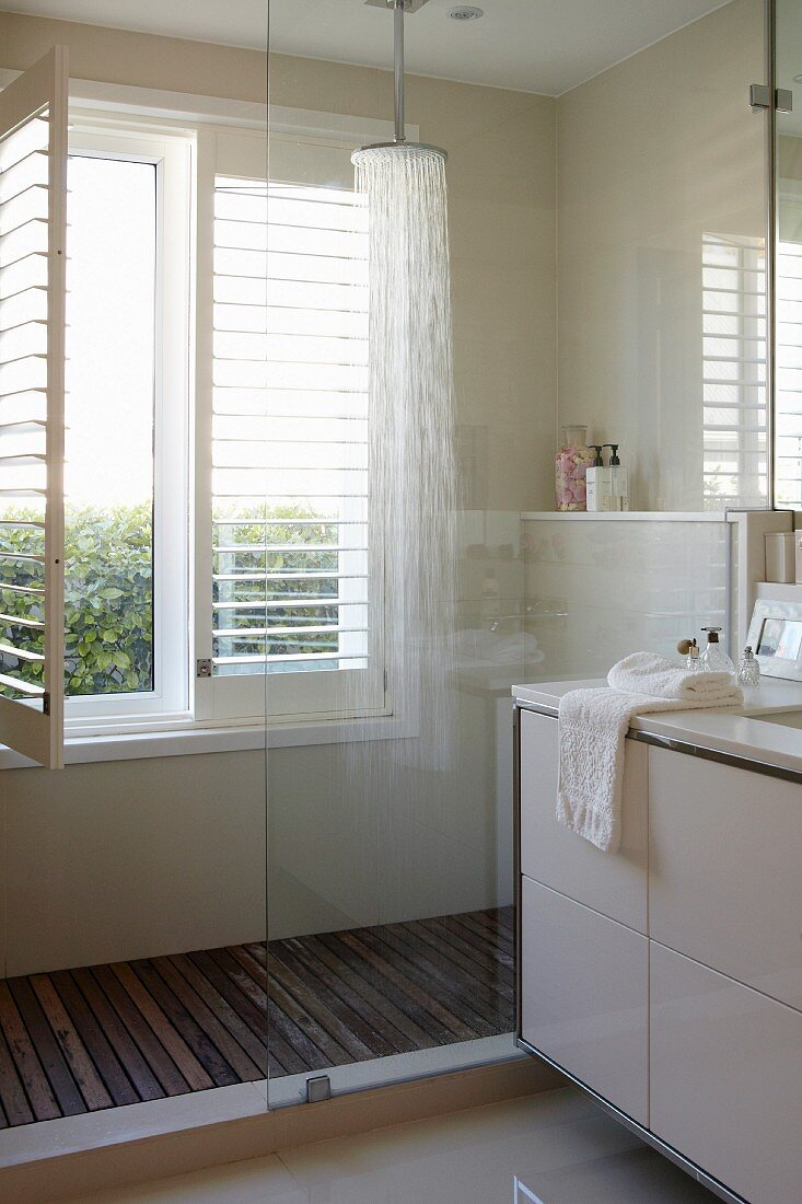 Detail of modern bathroom, partially visible washstand and glazed shower area next to window