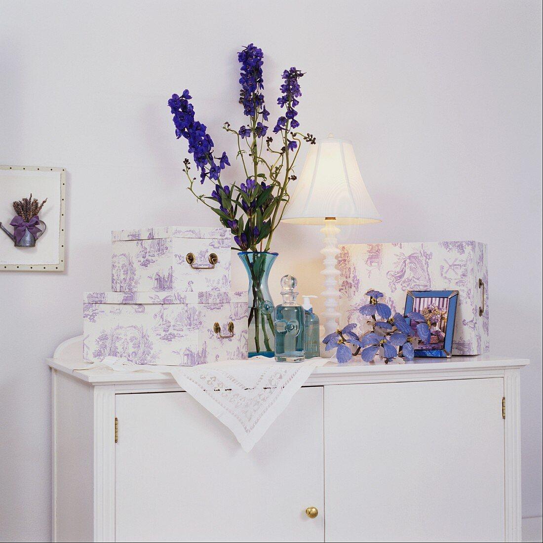 Schachteln mit lavendelfarbenem Toile de Jouy Muster und blaue Glasflaschen mit Rittersporn auf weisser Kommode