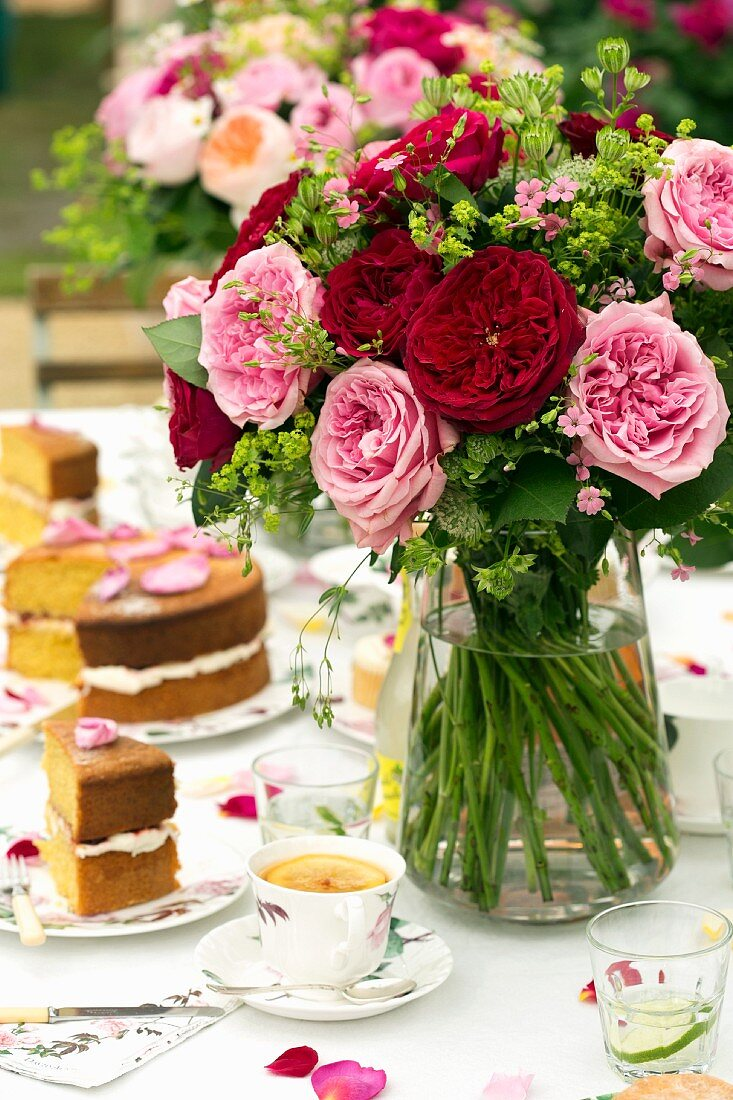 Bouquet of summer flowers on set table with cake and cups of coffee