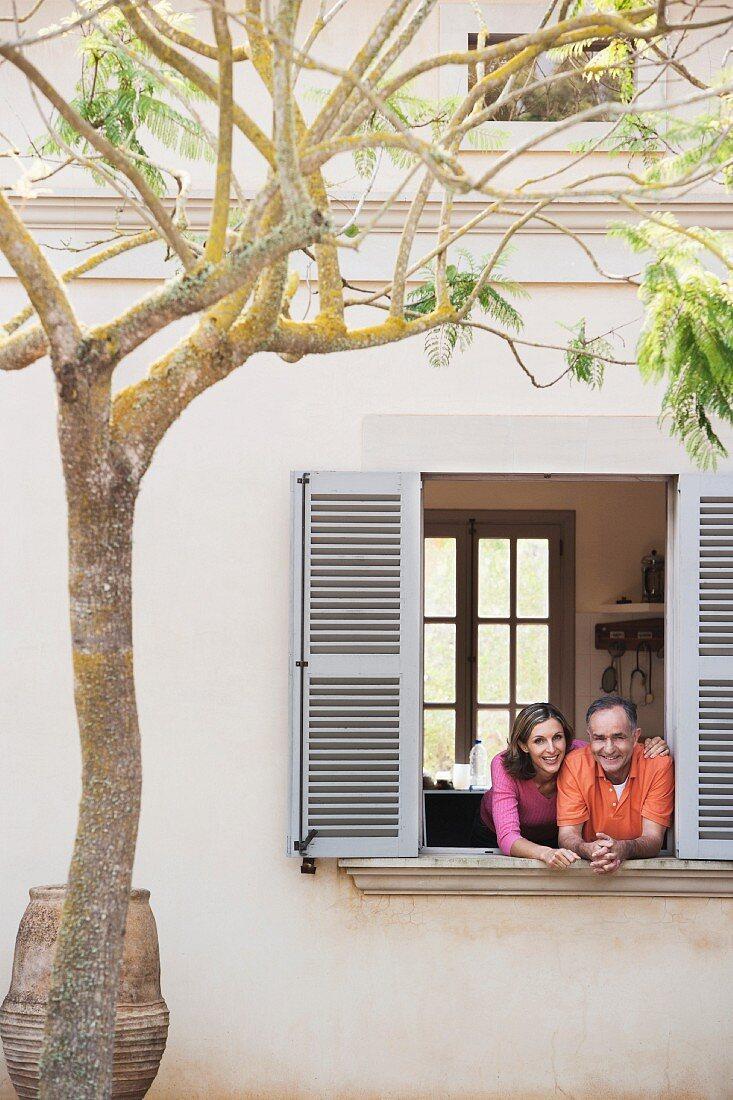Ein Paar schaut aus Fenster, vor dem Haus ein Mimosenbaum und ein mediterranes Tongefäss