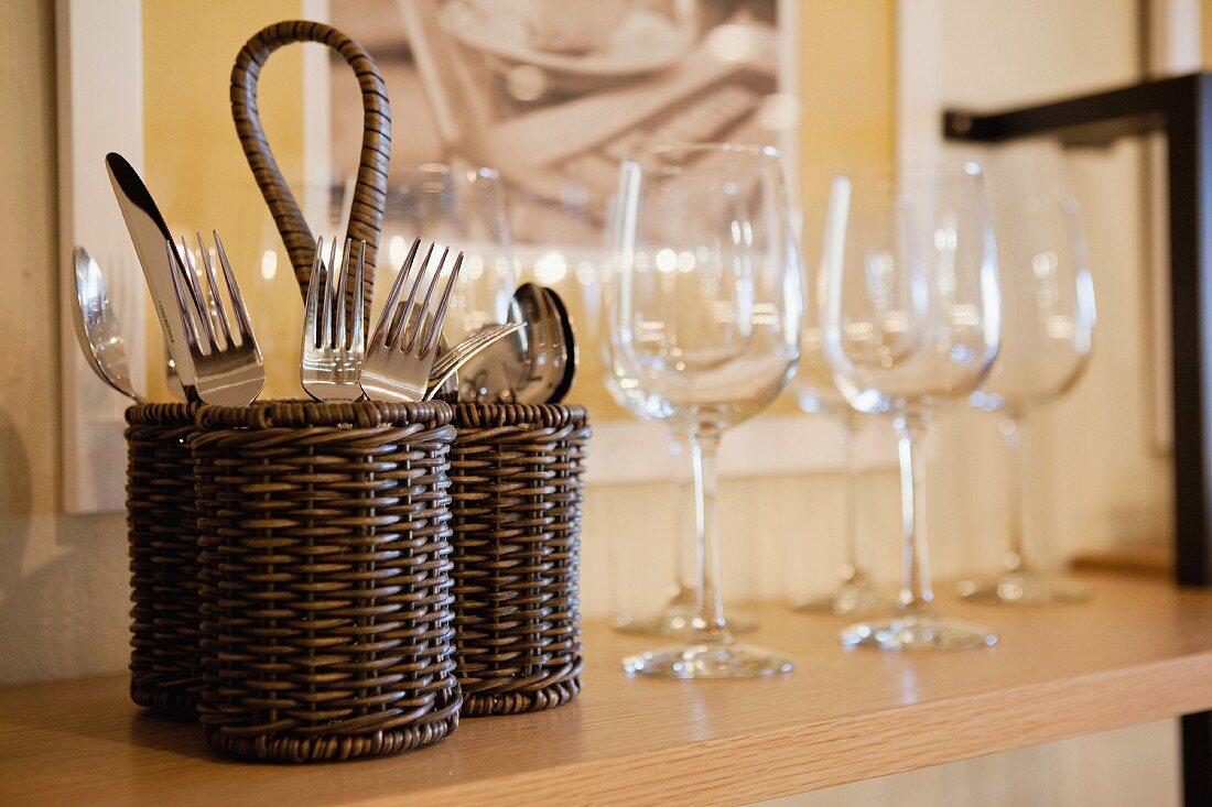 Besteck und Weingläser auf Regalbrett