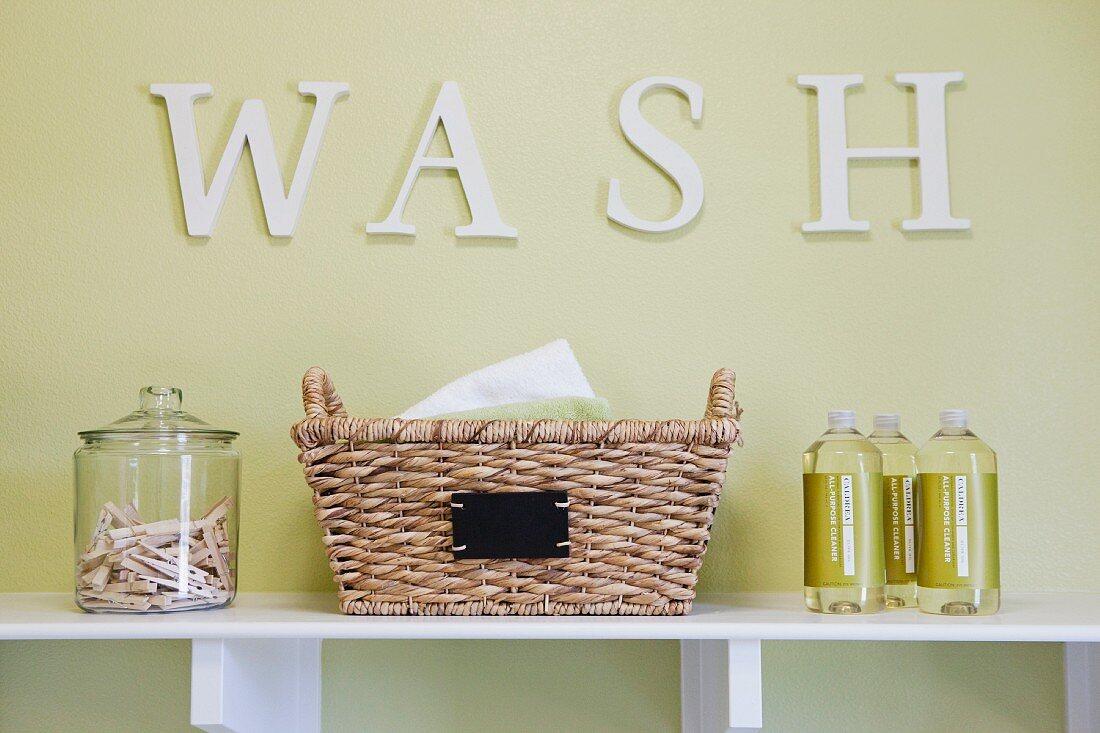 Schriftzug Wash in Waschküche über Regal mit Korb, Glasbehälter mit Wäscheklammern & Waschmittelflaschen