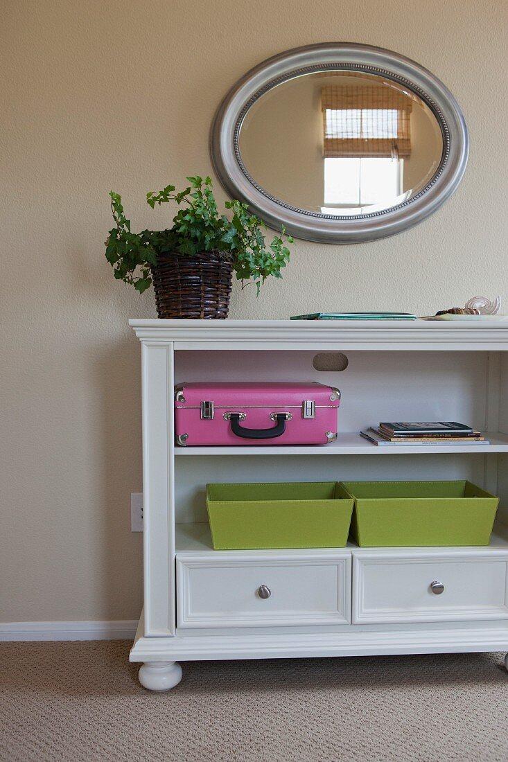 Weisses niedriges Regal mit zwei Schubladen unter ovalem silbernem Wandspiegel