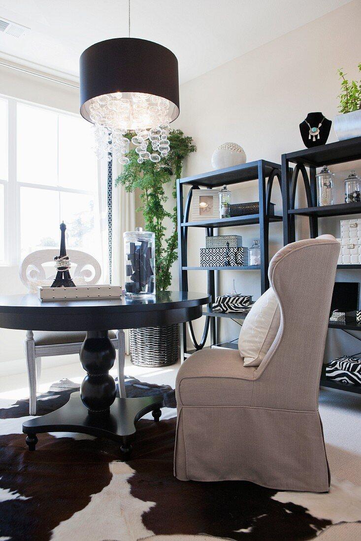 Wohnraum in schwarz-weiss mit rundem Tisch, Tierfell, Ohrensessel und Wandregalen
