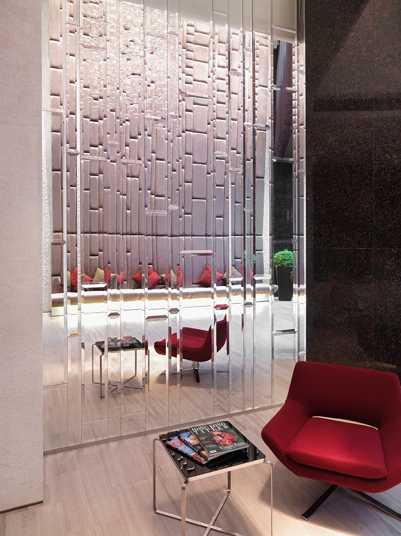 Modern red chair and table by patterned glass wall in house