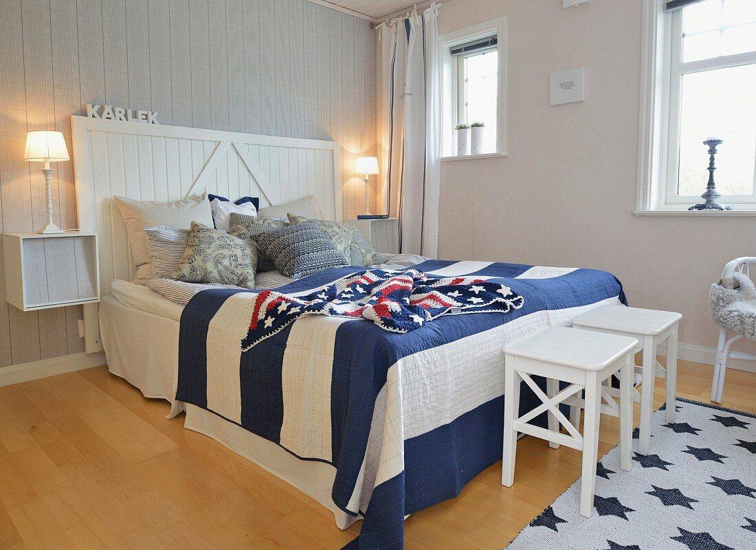 Maritimes Schlafzimmer mit blau-weiss gestreiftem Überwurf und gehäkelter 'Stars and Strips' Decke auf dem Doppelbett
