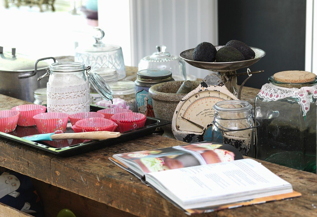 Cookery book, paper cake cases on baking tray and kitchen utensils on wooden table