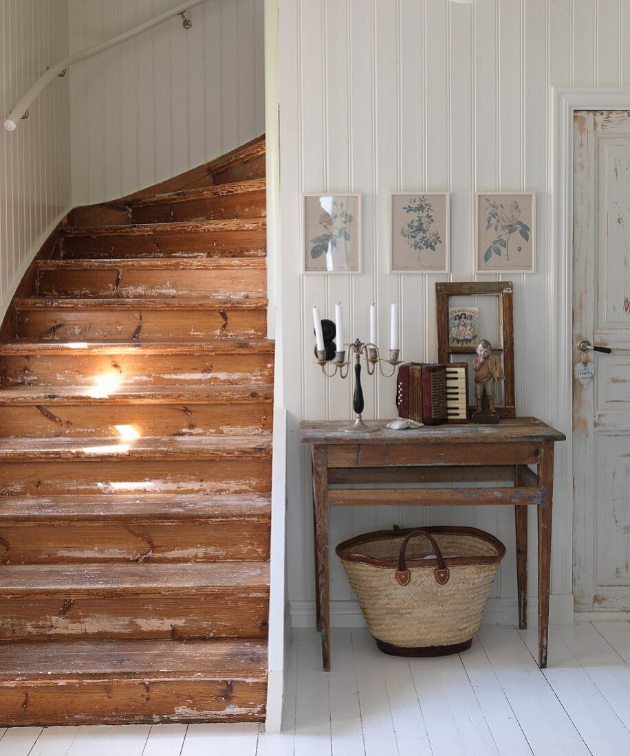 Candelabra and vintage accordion on simple table against white, wood-clad wall; rustic wooden staircase to one side