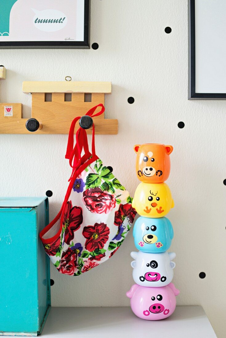 Stacking toys and train-shaped coat rack on white wall with black polka dots