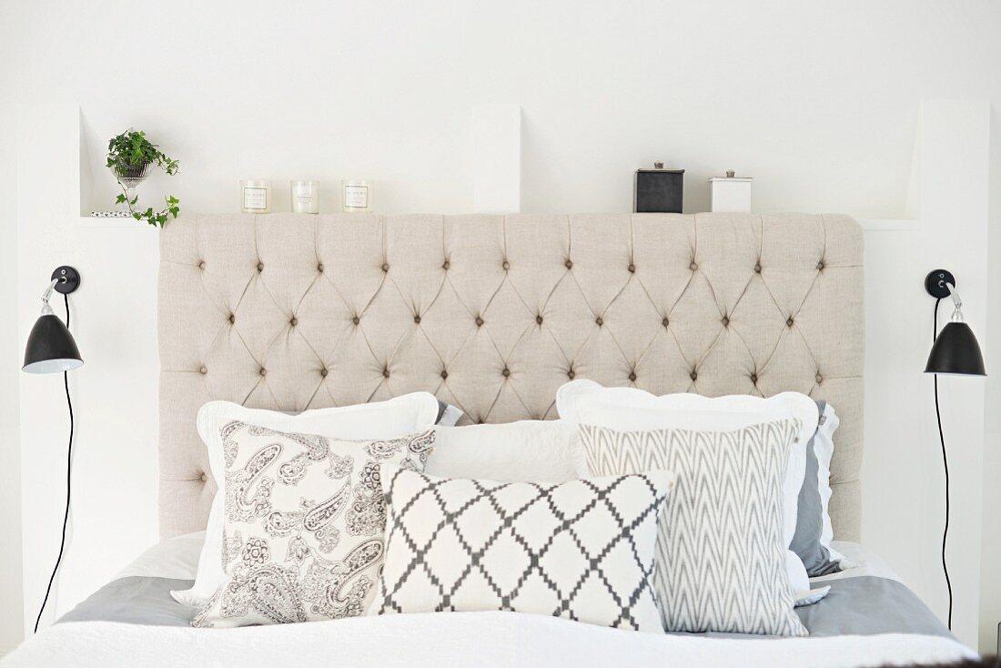 Doppelbett in Naturtönen mit Kissenparade und gepolstertem Kopfteil, flankiert von schwarzen Retro Wandleuchten