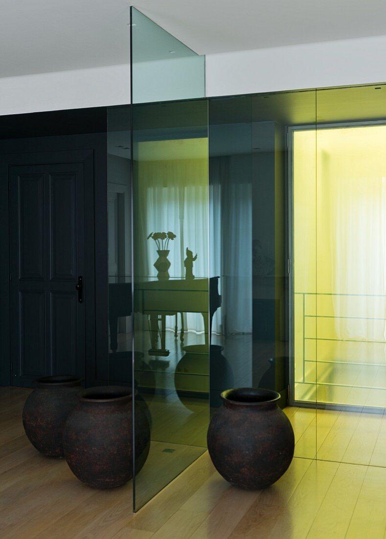 Schlichte Bodenvasen vor Glas Trennscheibe, gelbe Lichteinstrahlung im Durchgangsbereich