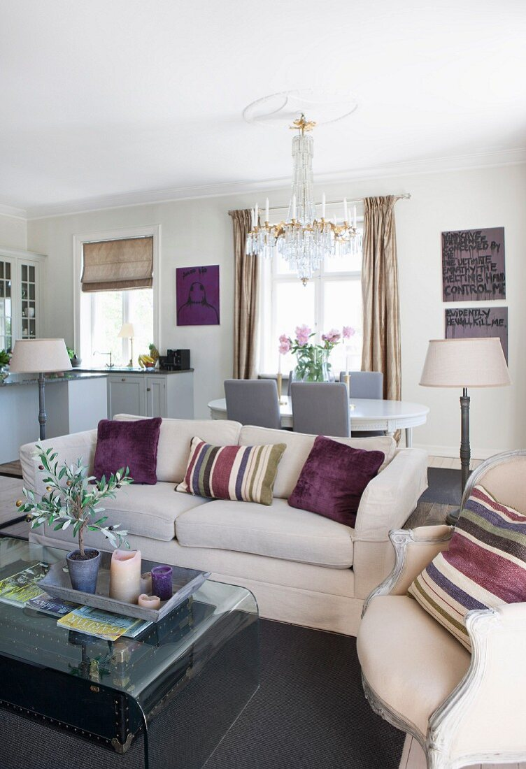 Striped scatter cushions on pale sofa and armchair around curved glass coffee table in open-plan interior
