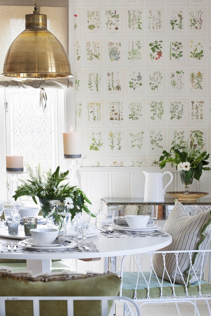 Table set with white crockery and vase of flowers in dining room with botanical wallpaper