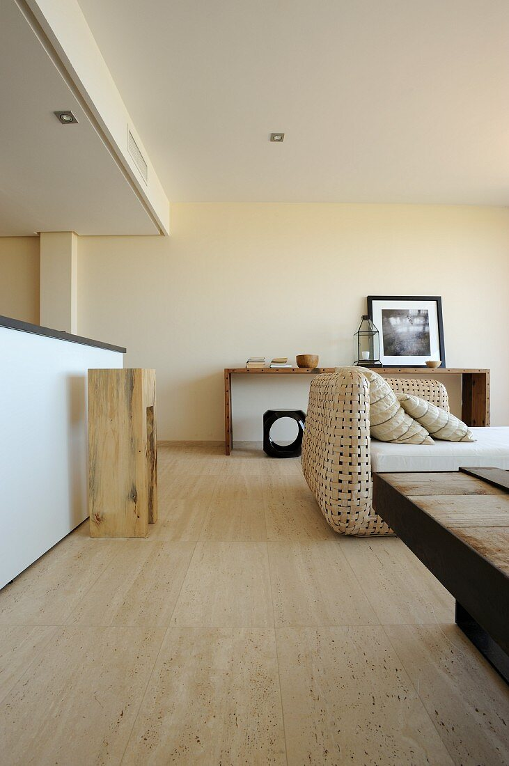 Open-plan interior with wood-block stool at kitchen counter and sofa with wicker frame; natural materials in pale shades