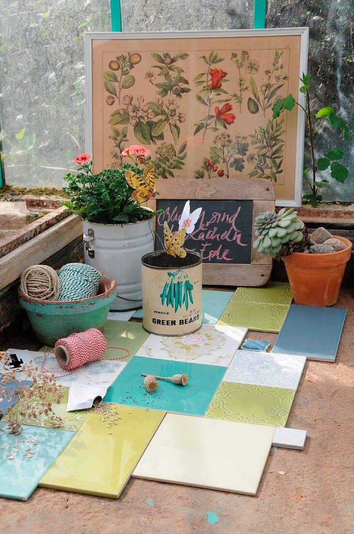Old tins, flowerpots, plants, reels of string etc. on work table with patchwork tiles
