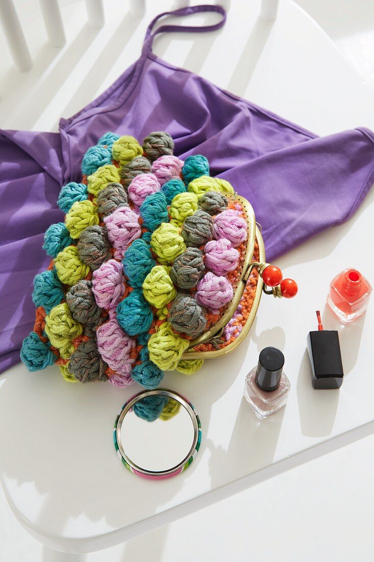 A purse with colourful bobbles next to a small mirror and bottles of nail varnish