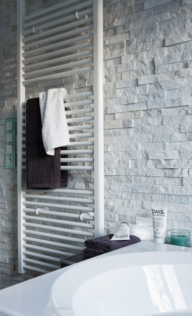 Towels hung on a white hand towel heater on the wall with decorative facing strips with a natural stone look with a partially visible bath tub in the foreground