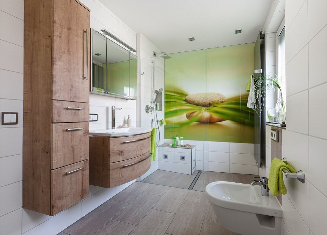 A modern bathroom with a refreshing natural design on a large glass panel on the wall in the shower with a tall built-in cupboard with a wooden effect next to a washstand with a drawer unit in the same design