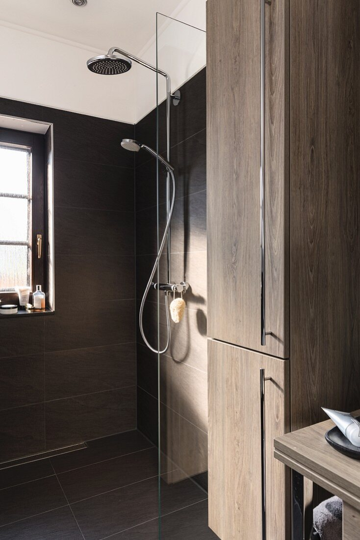 A floor-level shower with a fixed glass divider and two shower heads (one fixed, one moveable) on a tiled wall with a tall, oak-look cupboard in the foreground with stainless steel handles