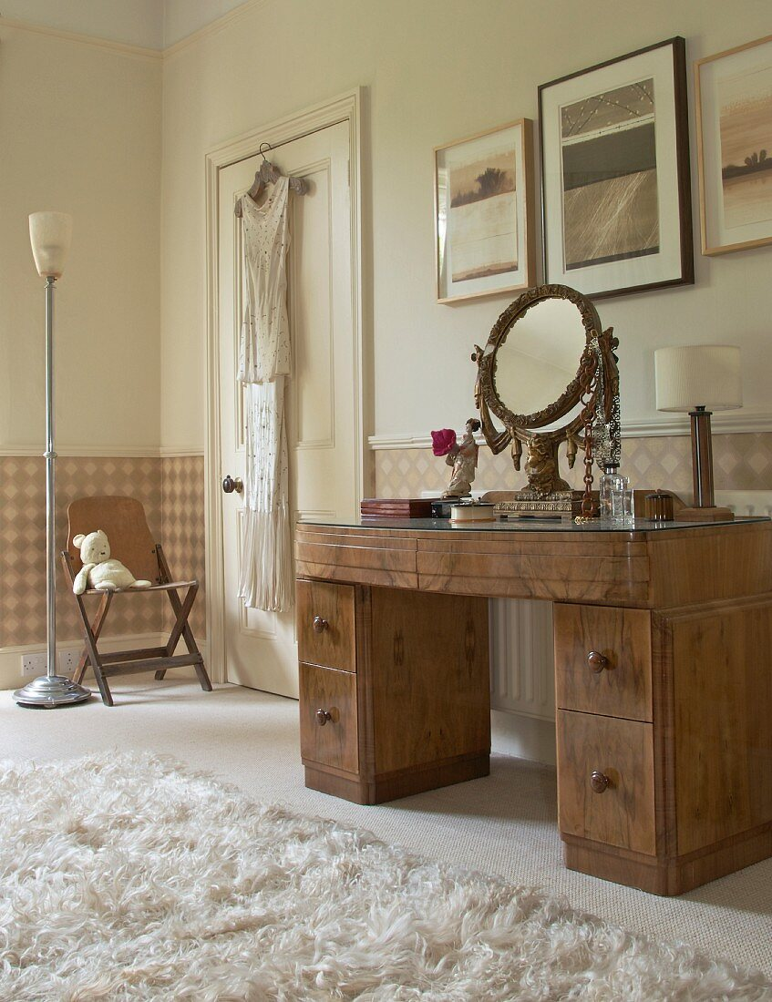 Bedroom in soft shades of beige and brown; pictures above antique, walnut dressing table with ornate brass mirror